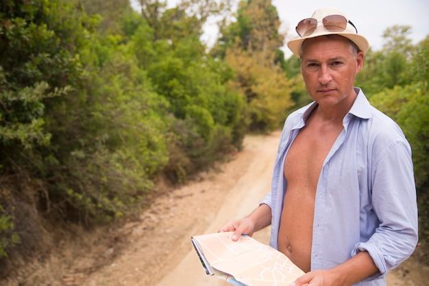 그는 라이프 스타일, 사람, 야외 및 휴가 개념-혼자 여행지도를 읽는 사람의 닫습니다
