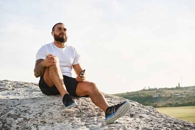 Крупным планом спортсмена человека, слушающего музыку во время прогулки в сельской местности