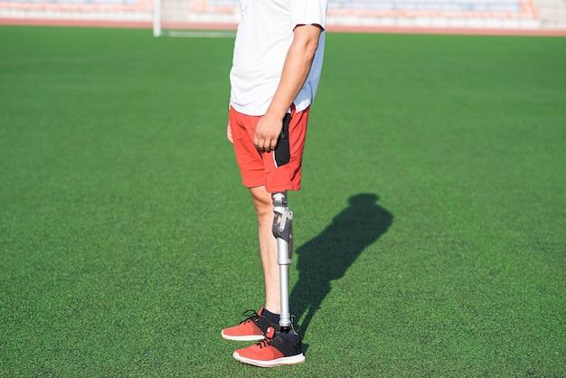 フィールドのスタジアムに立っている彼の足に義足を持つ男性アスリートのクローズアップ。スポーツコンセプト