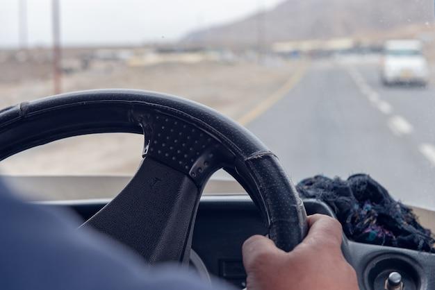 거리에서 자동차를 운전하는 동안 운전대를 잡고 남자 손의 닫습니다.