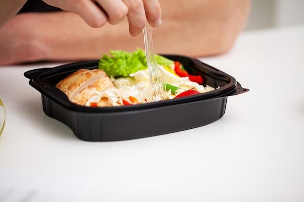 Крупный план человека, держащего коробку, полную белковой пищи для спортивного питания