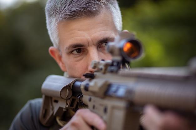 軍服でエアガンアサルトライフルを保持している男のクローズアップ