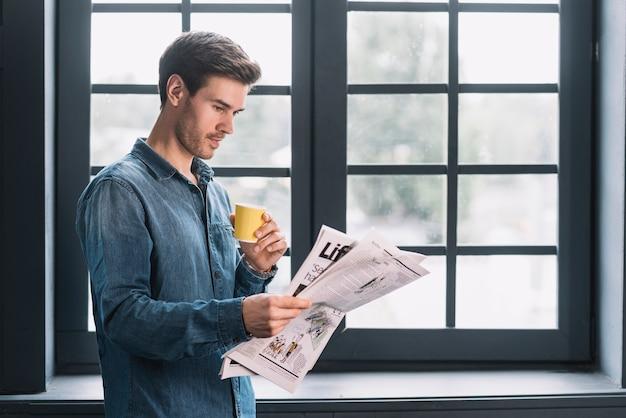 窓の近くに新聞を読んでいるコーヒーのカップを持っている男のクローズアップ
