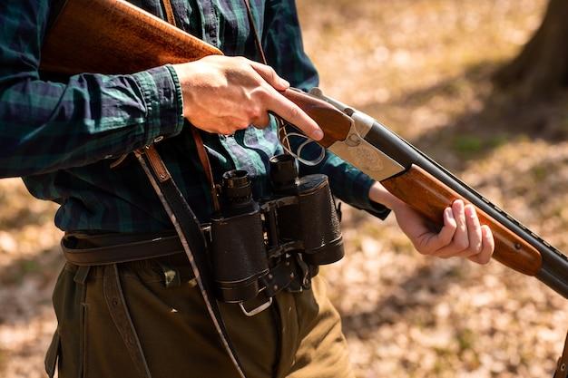 Крупный мужчина держит оружие в лесу