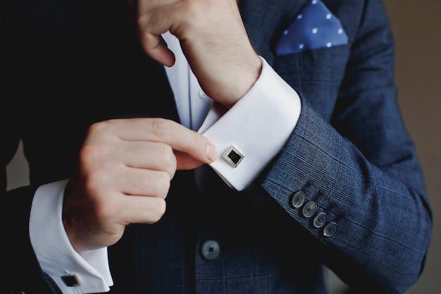カフスボタンを固定しているタキシードの男性のクローズアップ。