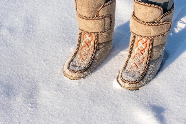Крупный план человека в валенках, стоящего на снегу