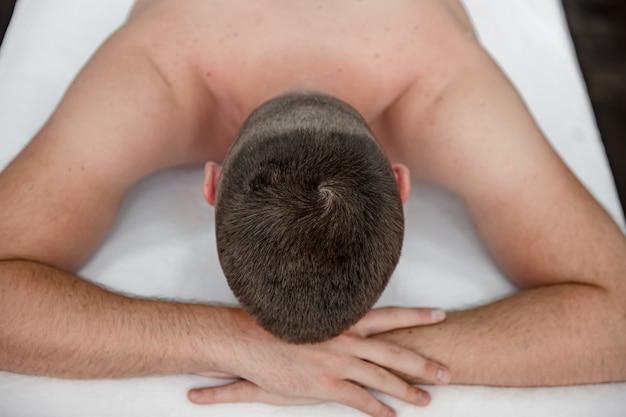 편안한 마사지를 받는 동안 소파에 누워 있는 남자의 클로즈업.