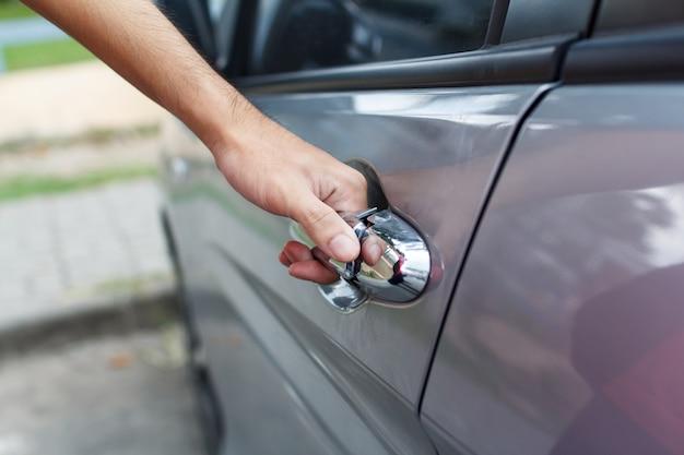 男のクローズアップは車のドアを開きます。