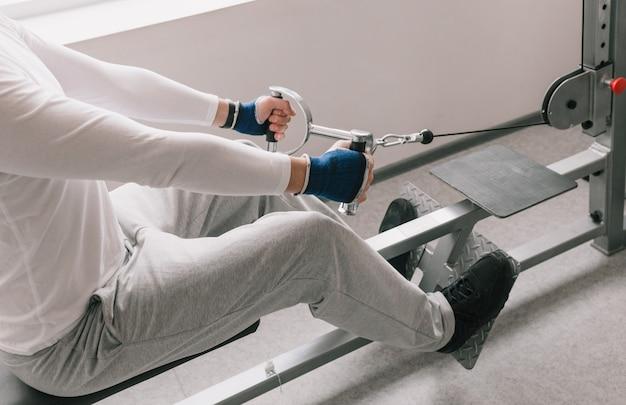 ウエイトトレーニングマシンでトラクションを実行している男性のクローズアップ。ジムでの激しいトレーニング