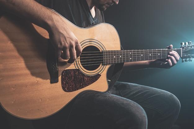 무대 조명이 있는 어둠 속에서 어쿠스틱 기타를 연주하는 남자의 클로즈업.