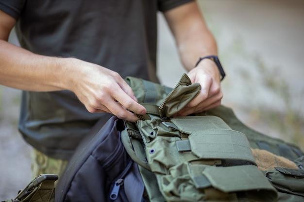 軍服でエアガンゲームの準備をしている男のクローズアップ
