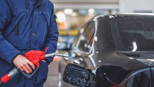 ガソリンスタンドで車にガソリンを汲み上げている男性のクローズアップ。