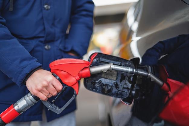 주유소에서 자동차에 휘발유를 펌핑하는 남자의 클로즈업.