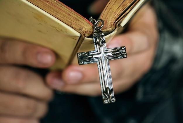Закройте человека, читающего библию с перекрестной висящей религией и концепцией убеждений