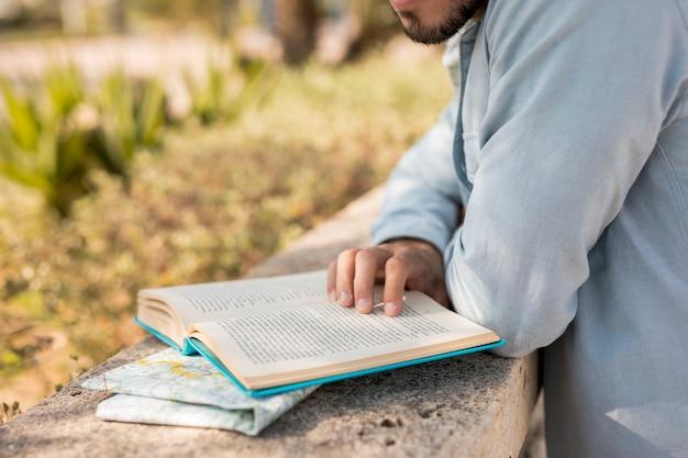 Крупный мужчина читает книгу