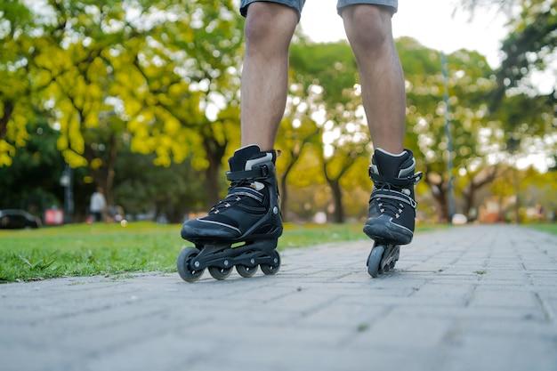 路上で屋外でローラースケートをしている男性のクローズアップ。スポーツの概念。