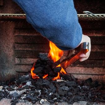 Крупный план руки человека, сжигающий уголь в барбекю