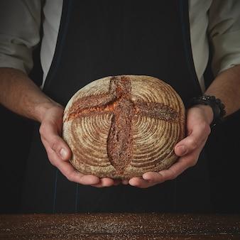 丸い暗いパンを持っている男の手のクローズアップ