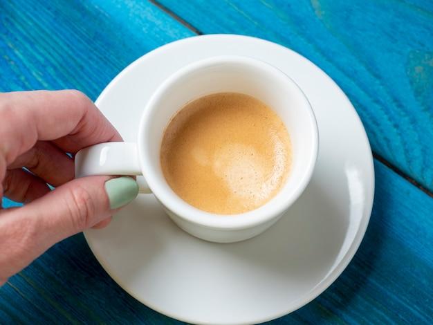 白い受け皿の上に芳香族エスプレッソの小さな白いカップを持っている男の手のクローズアップ。青い木製の背景、上面図、フラットレイ