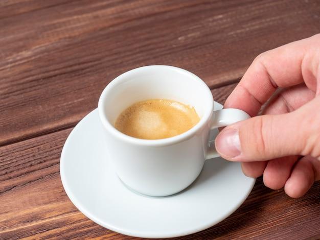 白い受け皿の上に芳香族エスプレッソの小さな白いカップを持っている男の手のクローズアップ。木製の背景、側面図。