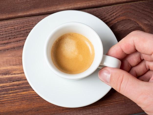 白い受け皿の上に芳香族エスプレッソの小さな白いカップを持っている男の手のクローズアップ。木製の背景、上面図、フラットレイ