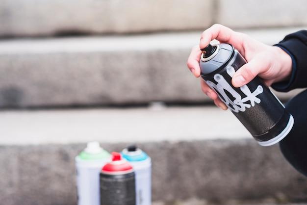 Крупным планом рука человека с граффити бутылку спрей