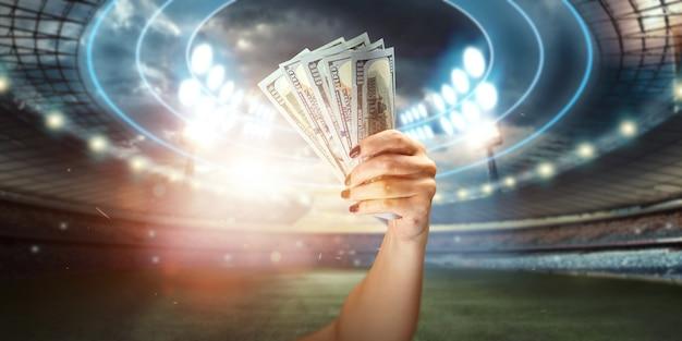 スタジアムの背景に米ドルを持っている男の手のクローズアップ。スポーツくじ、賭け、ギャンブルから利益を得るという概念。アメリカンフットボール。
