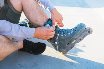 Close-up of a man's hand putting on rollerskate