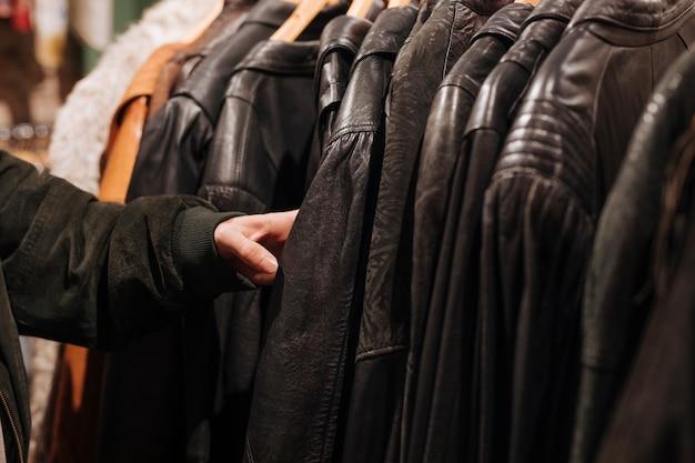 洋服店のレールの上の黒い革のジャケットに触れる男の手のクローズアップ