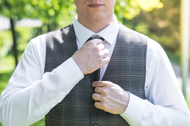 自然にネクタイを固定する男の手のクローズアップ