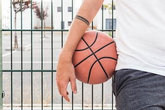 Close-up of a man's hand with basketball in front of fence