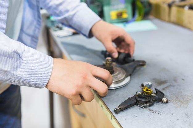 Крупный план руки человека с велосипедными частями в мастерской