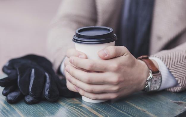 コーヒーを飲みながら人間の手のクローズアップ