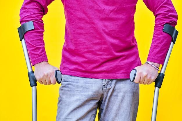 청바지와 보라색 티셔츠에 목발을 잡는 남자의 손 클로즈업.