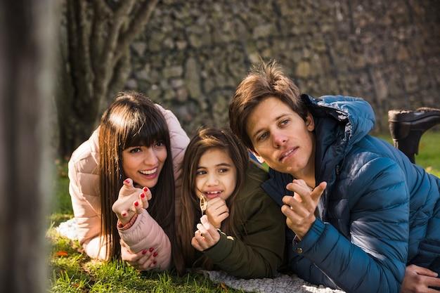 Крупный план человека, который показывает что-то своей семье в парке