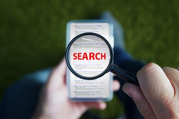 Закройте человека, сидящего и смотрящего через увеличительное стекло с красным письменным поиском слова на объектив на экране смартфона. использование мобильного интернета для поиска информации. просмотр в мобильном телефоне.