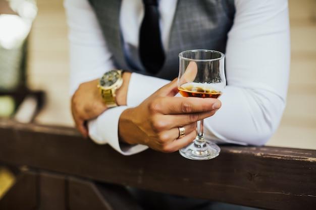 Крупным планом человека, сидящего за столом с бокалом коньяка.