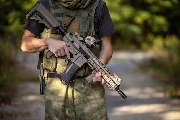 軍服を着たエアガンアサルトライフルで立っている男のクローズアップ