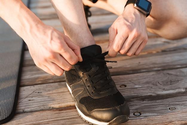 彼の靴ひもを結ぶ男のクローズアップ