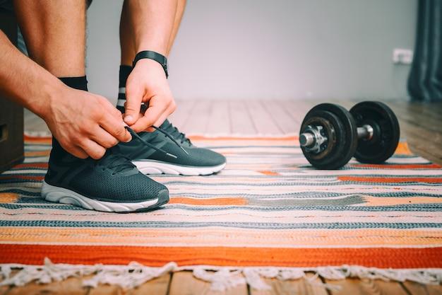 黒のスポーツスニーカーで靴ひもを結ぶ男性、彼の手にスポーツの黒の時計、近くの金属のダンベルのクローズアップ