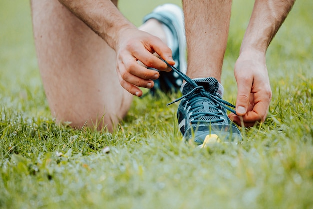 훈련 피트니스 전에 푸른 잔디 위에이 스포츠 신발에 신발 끈을 묶는 남자의 닫습니다