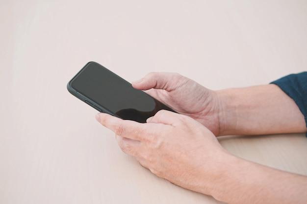 나무 테이블에 모바일 스마트 휴대 전화를 사용 하여 남자의 닫습니다.