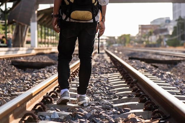 Крупным планом человека, идущего по железной дороге без пункта назначения