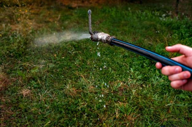 Крупный план мужчины, поливающего свой сад из шланга, извергающего воду