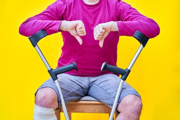 Крупный план человека с костылями, джинсами и фиолетовой футболкой, сидящего на стуле большим пальцем вниз.
