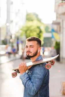 カメラを見てスケートボードを持つ男のクローズアップ