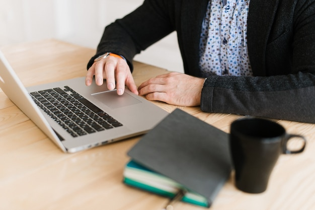 책상에 앉아 노트북에서 일하는 남자의 클로즈업. 일기가 탁자 위에있다. 집에있는 책상에서 일하십시오.
