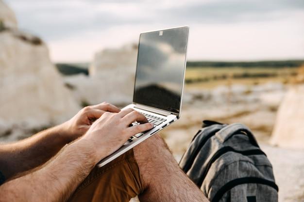 屋外でノートパソコンで作業する男性のクローズアップ。フリーランスのコンセプト。