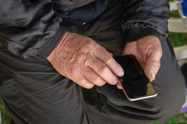 スマートフォンで触れている男のしわのある指のクローズアップ