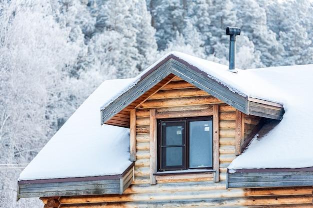 시골집에 mansard 플라스틱 창 확대, 지붕은 눈으로 덮여있다